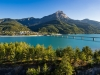 Summer panoramic view of Serre-Poncon Lake with Savines-le-Lac, its bridge and the Grand Morgon mountain peak. Hautes-Alpes, PACA Region, Southern French Alps, France