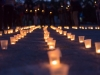A group of candles burning in street and people holding candles in the background. Day of Memory of the Bereaved